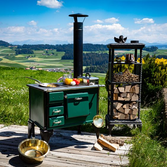 Wood-fired cooking stove in British racing green and black. An express fast-cooking hob and a cast-iron hob for frying food. The oven is in full working order.