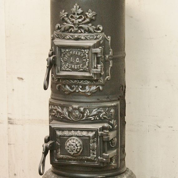 Cast-iron stove no. 1560, rare, lavishly decorated Sursee AG cylindrical stove with magnificent hood.