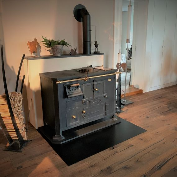 Original antique wood-fired cooking stove as a living-room focal point