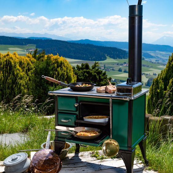 Wood-fired cooking stove in British racing green and black, a perforated grill pan can be used to cook on the hob while food can be grilled on the other side with a charcoal insert and a solid grill.
