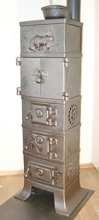 "Cast-iron stove no. 1379 - Perler Ofen/ Danish cast-iron stove ""DANA"", built 1921, with central symbol of a strong, powerful ox"